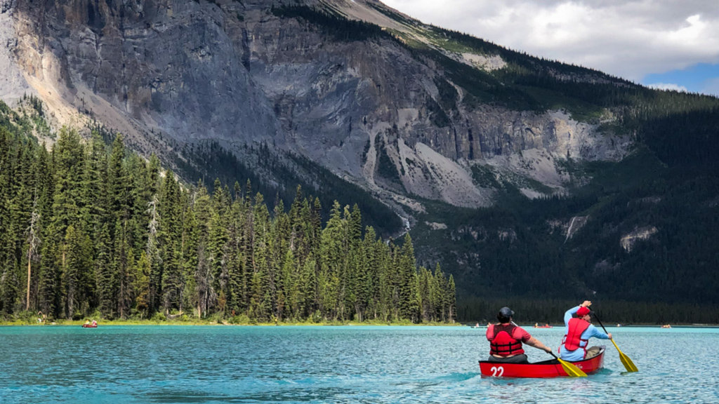 A person paddles a canoe on a lake with mountains in the background